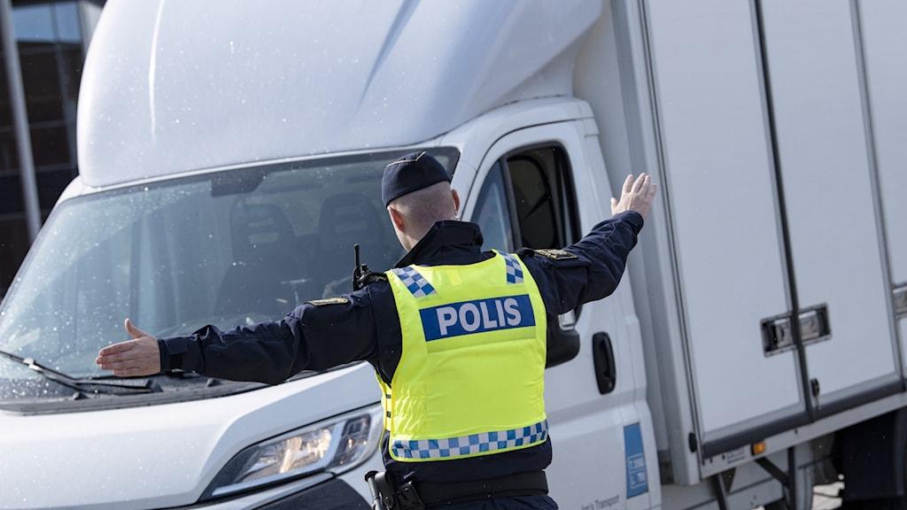En polis stoppar en lastbil
