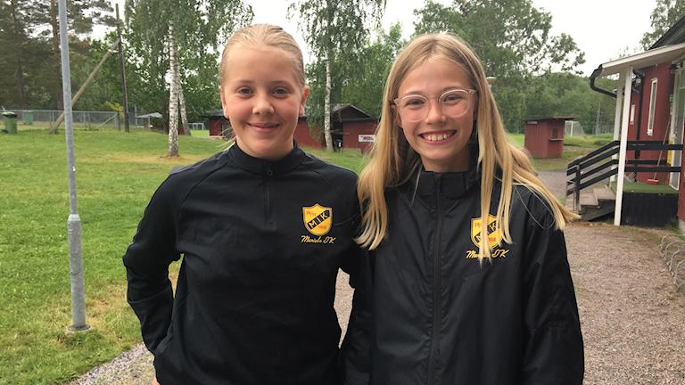 Maja Larsson och Lilly Bunninger vid en fotbollsplan.