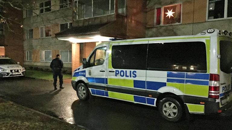 Polisbuss utanför hyreshus.