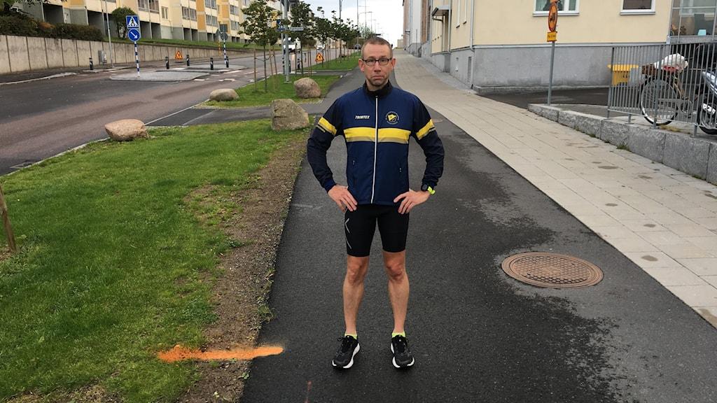En man står på en cykel- och gångbana i treäningskläder och visar ett orange streck i kanten som markerar 3 km.
