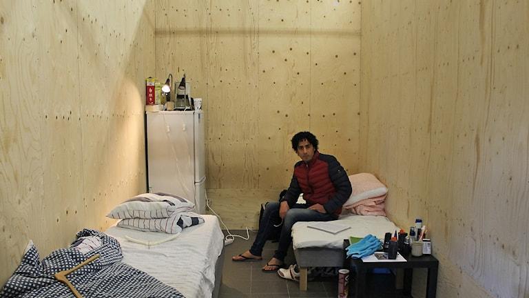 Alaa Alnasser i ett fönsterlöst träbås.