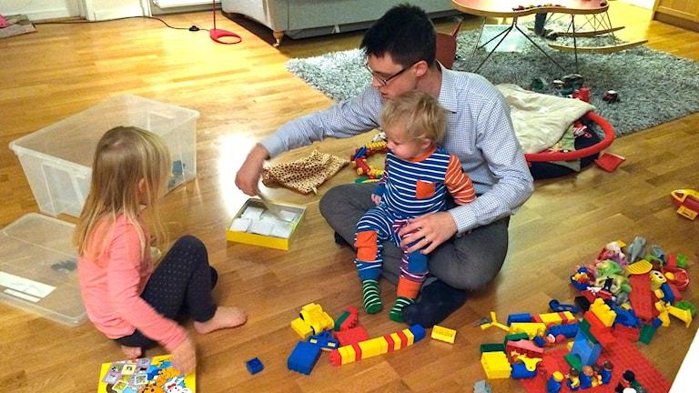 Gustaf Starlander sitter på golvet och leker med sina två barn.