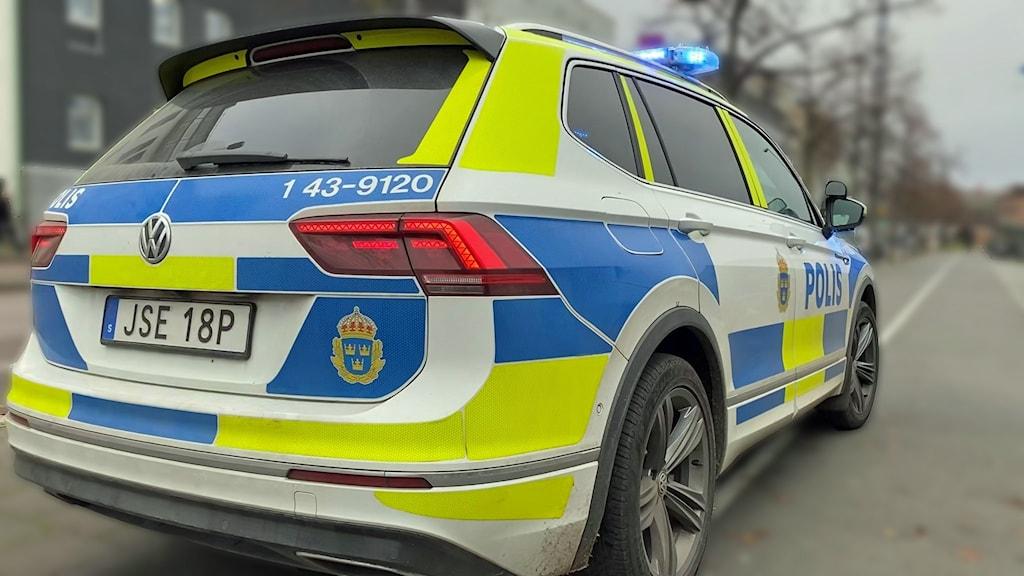 Polisbil parkerad med blåljus på.