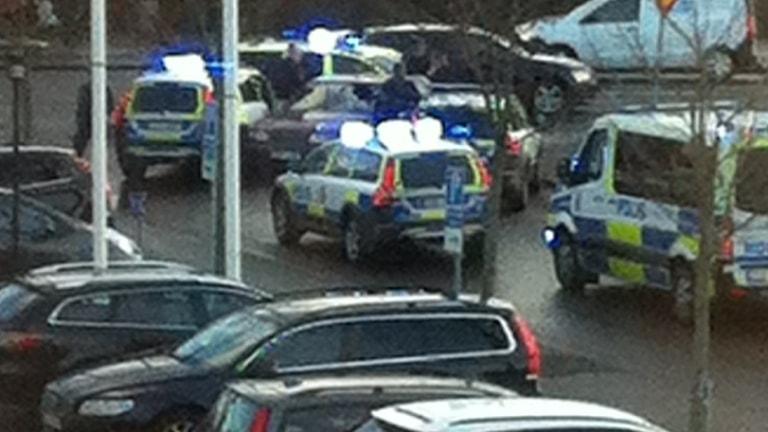 Fyra polisbilar med blåljus på en parkering.