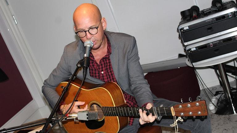 Niklas Lindkvist spelar gitarr och sjunger i en mikrofon.