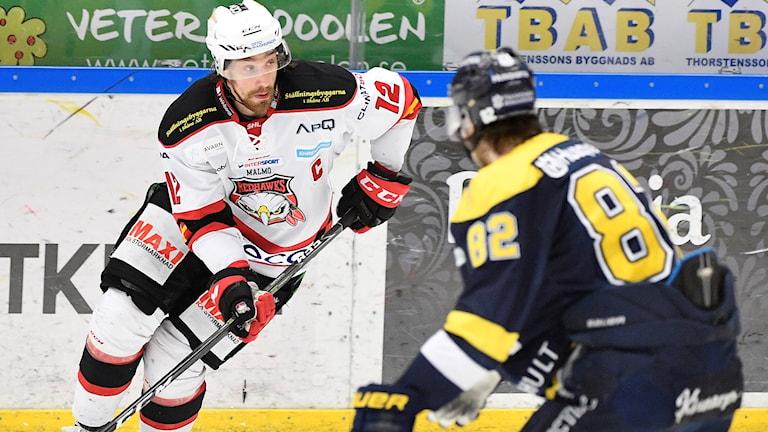 närbild på två hockeyspelare på isen