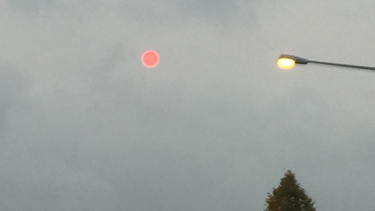 En röd sol på en molnig himmel.