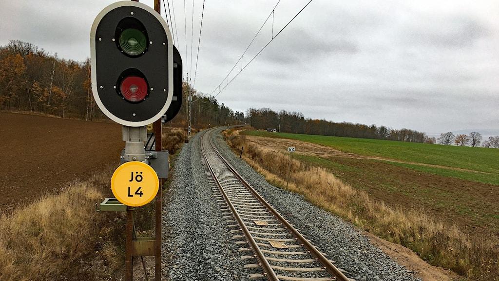 En säkerhetssignal visar rött bredvid ett tomt järnvägsspår.