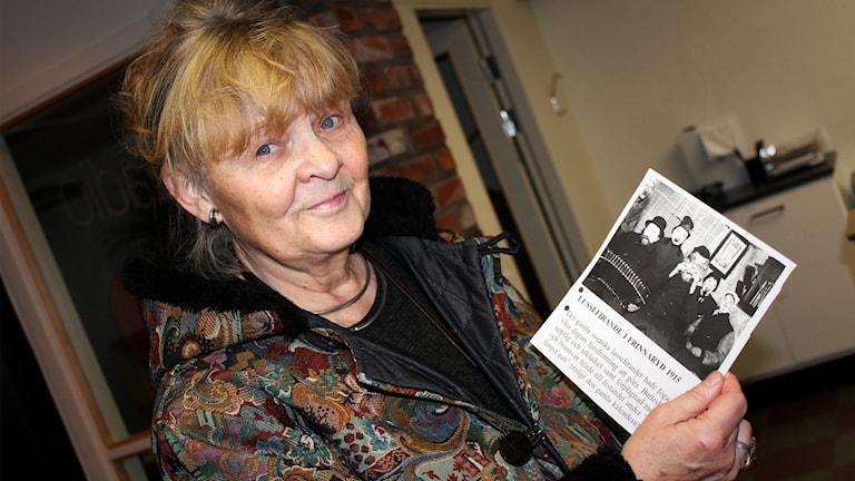 Eva Londos håller i ett foto som visar ett gammalt lussefirande.