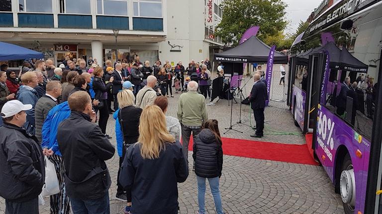 Publik i Värnamo tittar på nya laddhybridbussen.