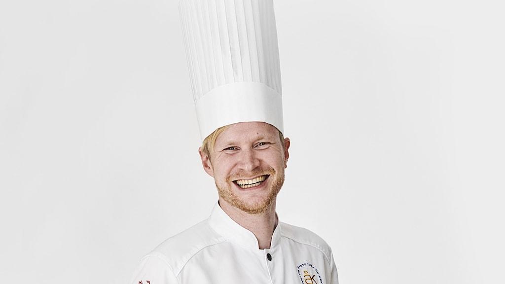 En man i hög vit kockhatt ler stort