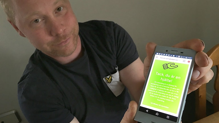"""Marcus Sjöberg håller fram sin telefon där texten """"Tack, du är en hjälte"""" syns."""