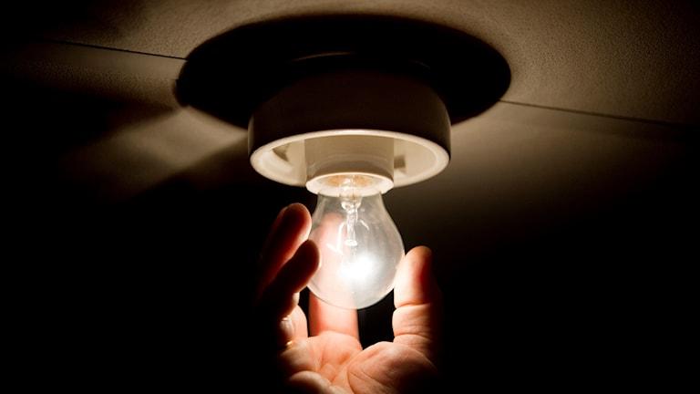 En hand skruvar på en glödlampa som lyser.
