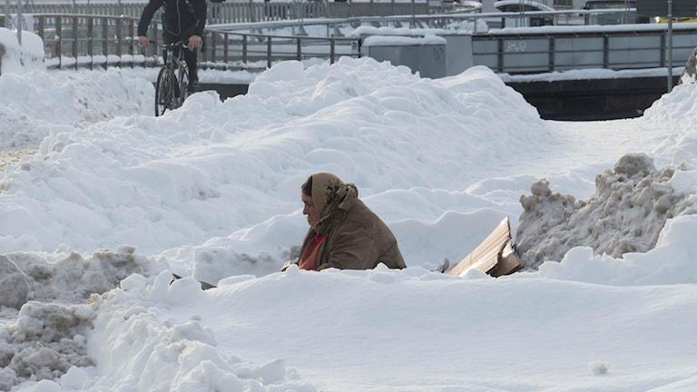 En kvinna sitter och tigger i ett snölandskap.
