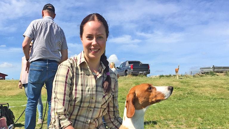 Angelica Åhlfeldt med sin hund, i bakgrunden grönt gräs och en pick-up.