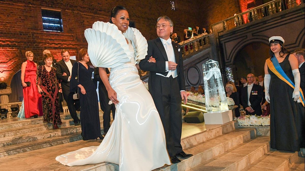 Alice Bah Kuhnke har på sig en vit klänning med stora snäckliknande armpuffar.