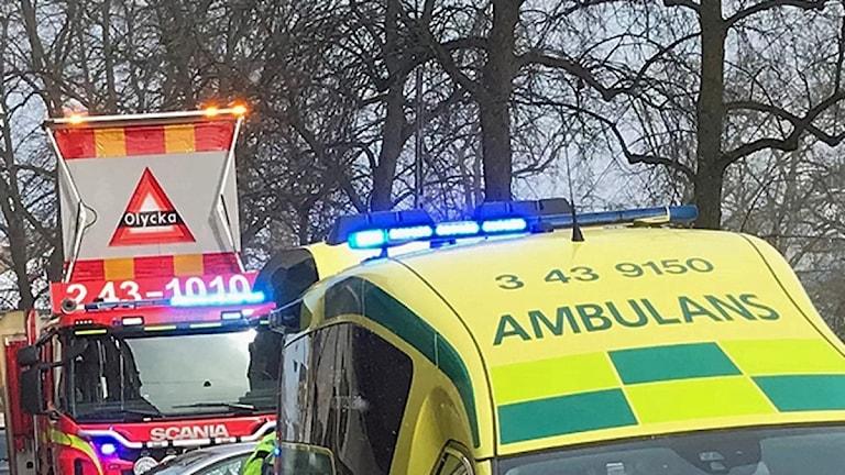 En brandbil och ambulans vid en olycksplats.