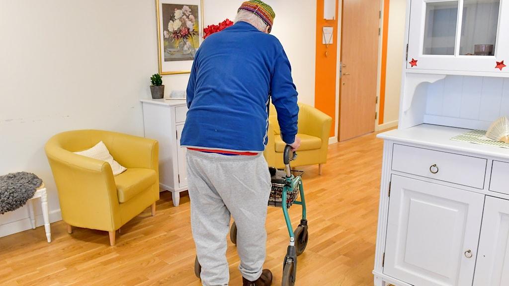 Man på ett äldreboende går med sin rollator.