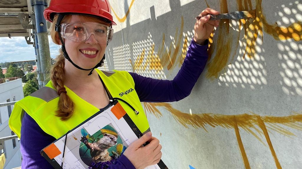 Nina Valkhoff håller en pensel med  gul färg. Röd bygghatt och en gul väst, håller sin design i handen och befinner sig på en byggställning.