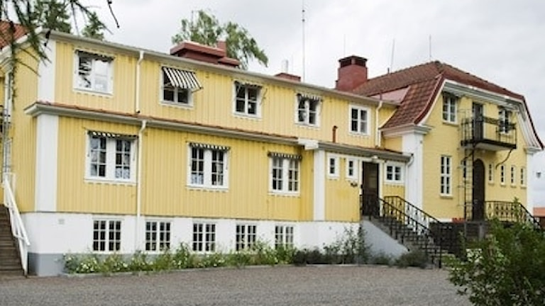 En stor byggnad med gul träpanel.