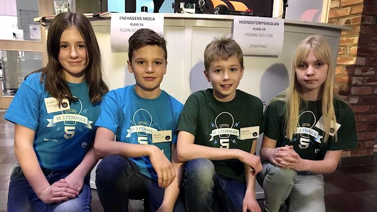 Fyra femteklassare sitter på knä framför ett podium.