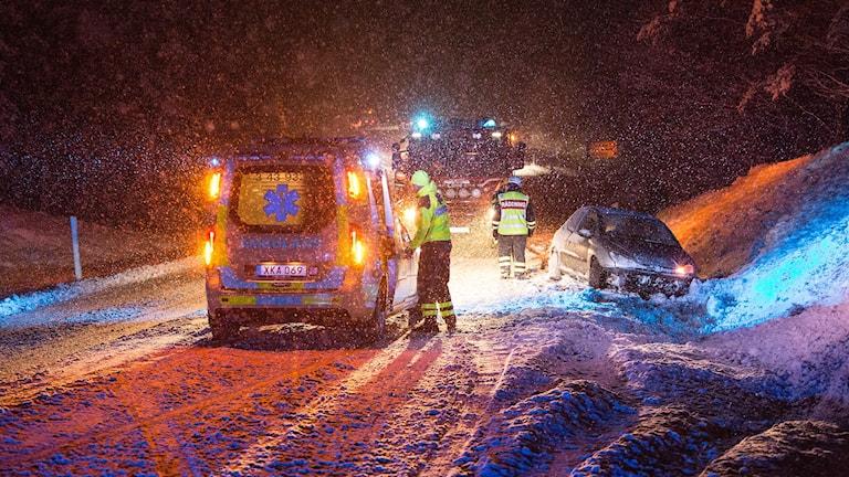 Räddningspersonal arbetar i snöyra med en bil som kört i diket i Bondarp mellan Aneby och Sunhultsbrunn.