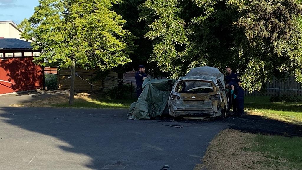 Utbränt bilvrak parkerad på asfalt. Grön presenning intill bilen. Tre blåklädda polismän med gröna handskar intill bilen. Dagsljus.