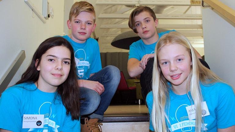 Fyra barn sitter i en trappa