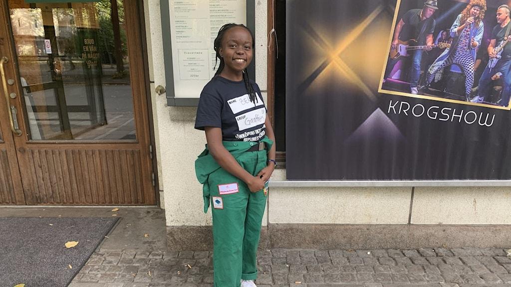 En ung tjej står utanför en pub. Hon är klädd i en grön studentoverall.