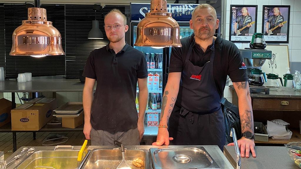 Två man står i ett restaurangkök.