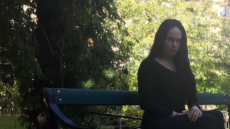 Anastasia sitter på en bänk