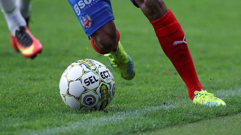 Ett par ben i fotbollsstrumpor och en fot som måttar mot en fotboll.
