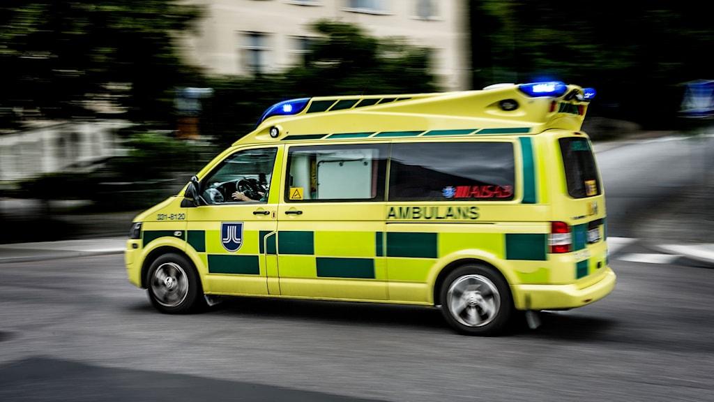 En gul ambulans kör på vägen.