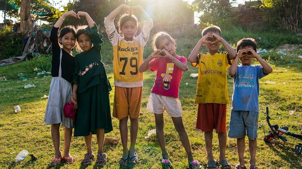 Sex barn står ute i naturen och formar hjärtan med händerna.