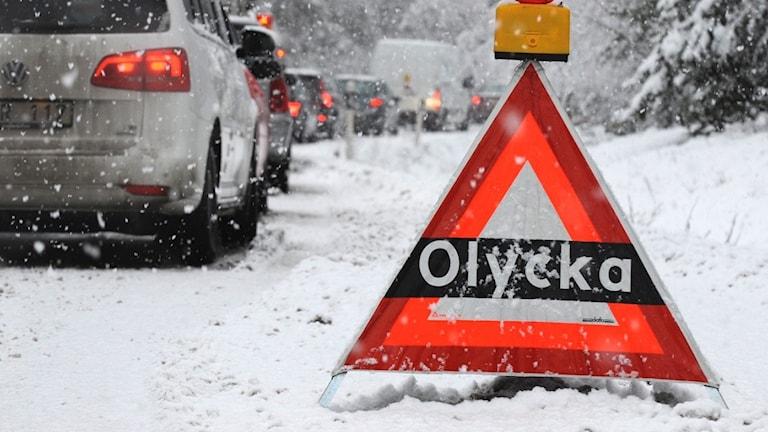 En olycksskylt vid en snöig väg.