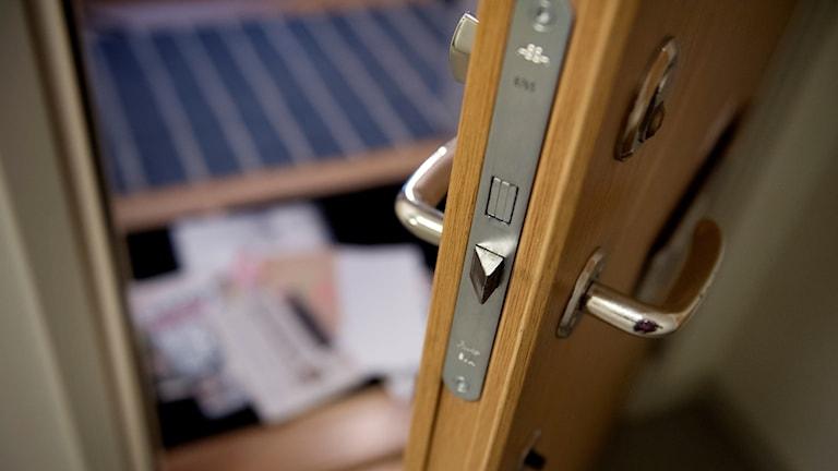 En lägenhetsdörr där brev ligger innanför tröskeln.