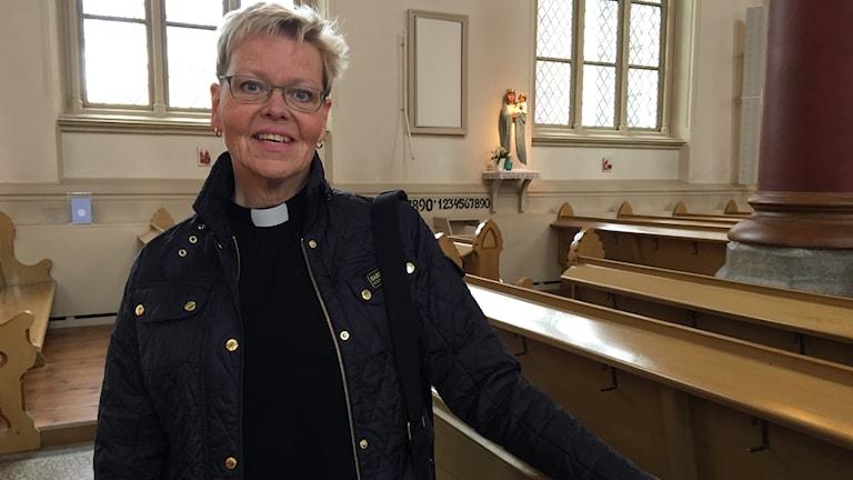 Kyrkoherden Ann Allden vid en kyrkbänk