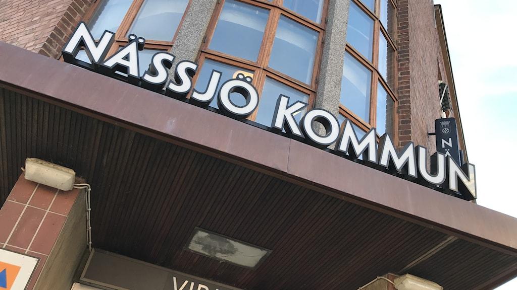 """En bild på entrén till Nässjö kommuns bruna kommunhus, där det står """"Nässjö kommun"""" med vita bokstäver ovanför ingången."""