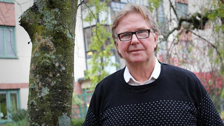 Jan Pilefelt står bredvid ett träd.