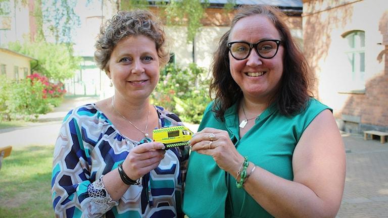Eva-Lotta Lager och Mia Frisk håller i en liten lekaskambulans.