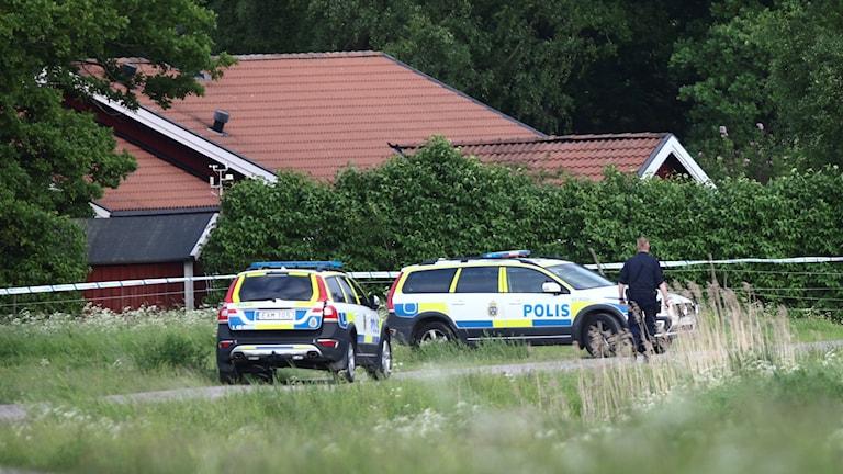 Två polisbilar står utanför ett avspärrat hus.