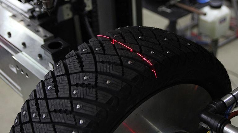 Ett svart nydubbat däck sitter i maskinen. En röd laserstråle lyser på däcket.