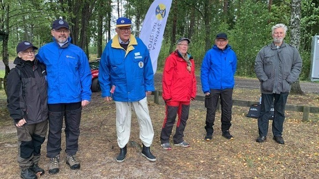Två kvinnor och fyra män står i skogen och tittar in i kameran.