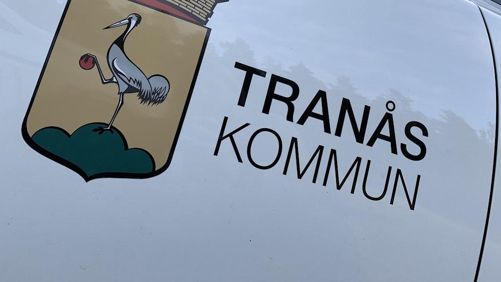 """Texten """"Tranås kommun"""" i svarta bokstäver mot en vit bakgrund och kommunens logga med en trana till vänster om texten."""