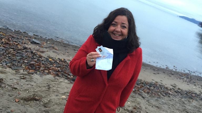 Sonja Stankovic på stranden. I handen håller hon sitt ID-kort.