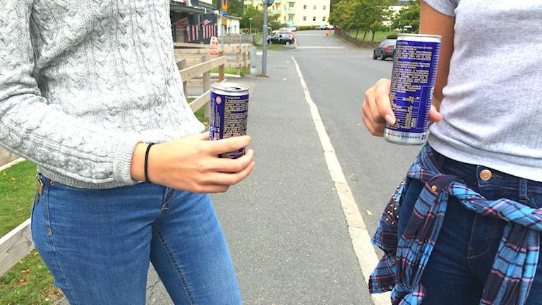 två tjejer står och håller i var sin energidryck
