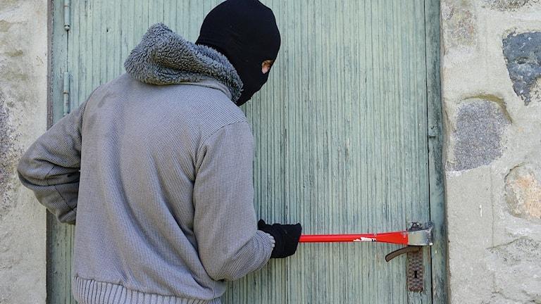 Person i rånarluva bryter upp en dörr.