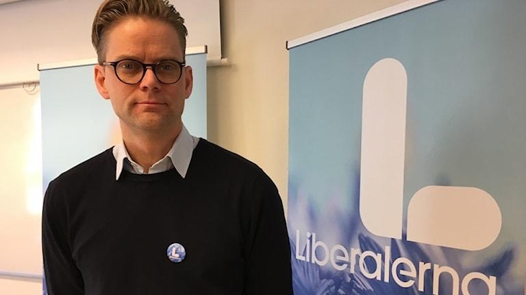 Jakob Olofsgård står vid en skylt med Liberalernas logga.