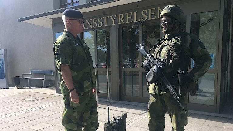 En soldat och en en annan person från försvarsmakten står och kollar på varandra.