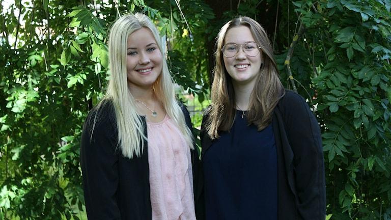 Två tjejer står framför ett träd.